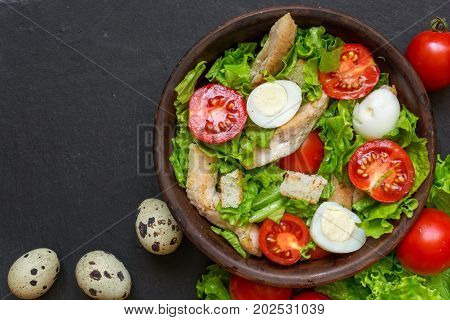 Fresh salad caesar with chicken quail eggs tomatoes and lettuce in a bowl on dark stone background with copy space. top view