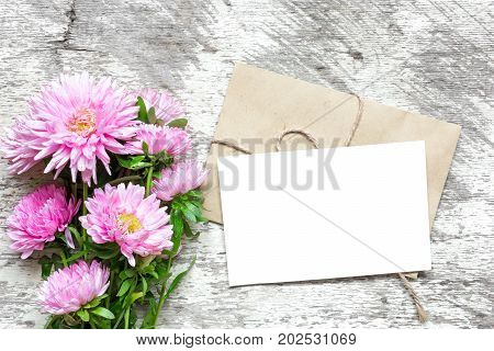blank white greeting card with pink aster flowers bouquet and envelope on white wooden background. top view. mock up