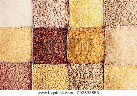 Assortment groats as decorative background. Wheat pearl bulgur millet rice couscous semolina corn grits buckwheat quinoa. Top view closeup.