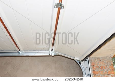 Install Garage Door Metal Post Rail and Spring Installation and Garage Ceiling. Spring Tension Lifts Section Garage Door Panel that Motor does not have to Lift Entire Weight.