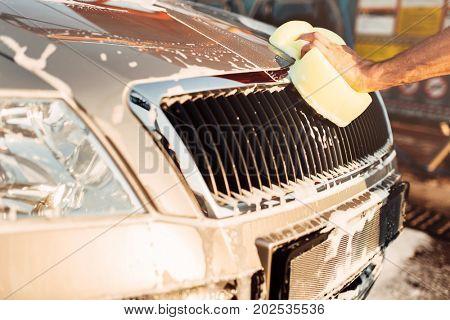 Male hand rubbing the car with foam, carwash