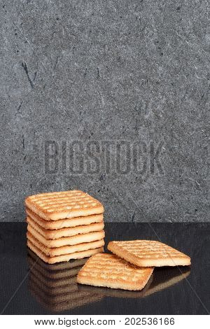 A vertical stack of square sugar cookie are laid on a black background with a reflection with copy space