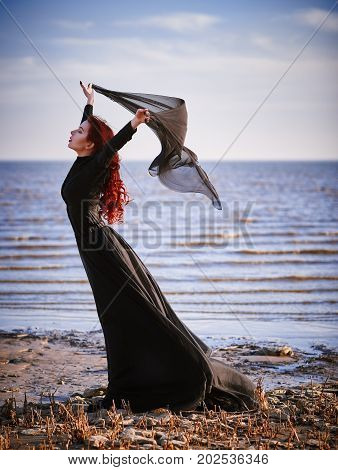 Beautiful sad goth girl with cloth in hands standing on the sea shore