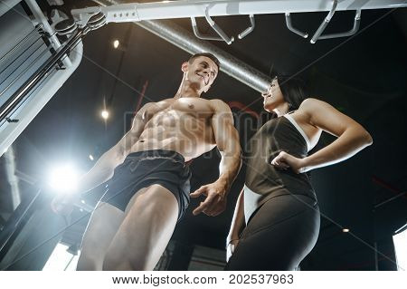 Handsome young muscular Caucasian man and woman working out training in the gym gaining weight pumping up muscles and poses