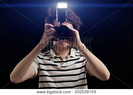 Photographer using flash on his camera in dark room