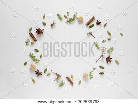 Christmas tree twigs cardamom seeds and anise stars some small weathered fallen leaves and snowflakes to remind how cosy home smells when winter comes and it's cold outside flat lay background with a space for a text