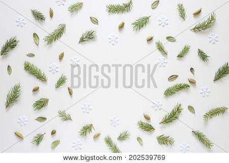 Christmas tree twigs cardamom seeds some small weathered fallen leaves and snowflakes to remind about cosy winter home smells when it's cold outside flat lay background eith a space for a text