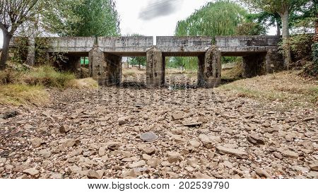 Wide angle view of drought river and bridge