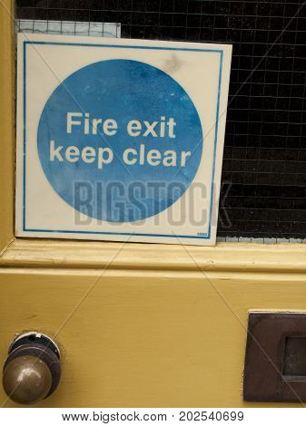 Fire exit keep clear mandatory self adhesive sticker on rear entrance door to retail unit
