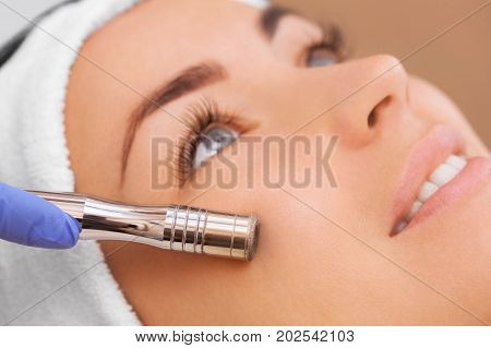 The doctor-cosmetologist makes the procedure Microdermabrasion of the facial skin of a beautiful young woman in a beauty salon.Cosmetology and professional skin care.