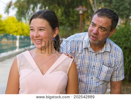 Girl teenager and her father quarrel outdoors