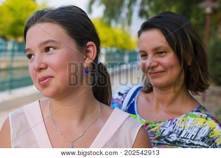 Thoughtful teenage girl and her mother outdoors portrait