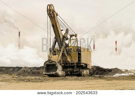 Big bucket mining excavator on a crawler track against a background of dense factory smog and fog with smoking chimneys. Heavy industry background. Excavator with mechanical drive and flexible suspension of work equipment.