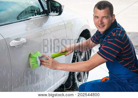 the man in the uniform washes the car with a brush in the foam on the car wash