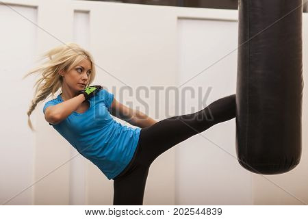 Young Girl Doing Boxing Workout In The Gym. Female Fighter Smash Punching Bag