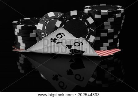 two small cards in poker under the poker chips reflected on black background