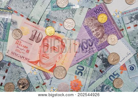Singapore Dollar On Top Of Malaysian Ringgit Currency On Background