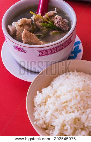 Pork Spare Ribs Soup With Rice On Red Table Background
