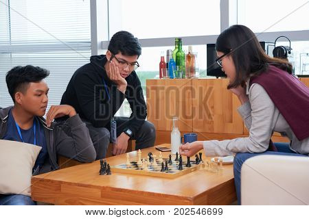 Pensive young people pondering over new move in game of chess