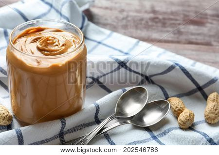 Jar with creamy peanut butter on napkin