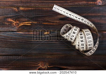Close up tailor measuring tape on wooden table background. White measuring tape shallow dept of field.