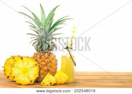 Bottles of pineapple juice with sliced pineapple fruit on wooden table with white background summer fruit drink concept
