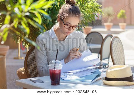 Closeup Image Of Young Good-looking Caucasian Female Checking Important Papers For Work Trying Not T