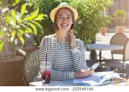 Closeup Image Of Young Beautiful Female Wearing Hat Sitting At Table In Street Cafe In Summer, Holdi