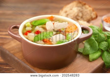 Casserole with delicious turkey soup on table