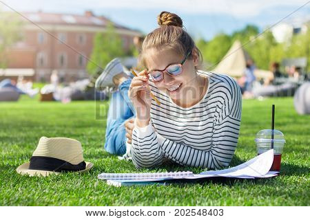 Outdoor Portrait Of Good-looking Smiling Female Lying On Green Grass In City Park While Doing Hometa