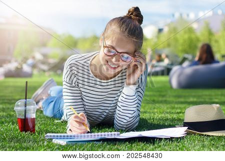 Closeup Of Good-looking Student Girl On Grass In Park, Her Head Bent Towards Notebooks Where She Wri