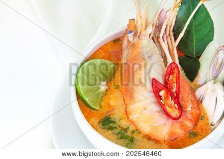 Close up Asian Spicy soup with shrimp in white bowl famous Thai food cuisine calling Tom Yum Kung