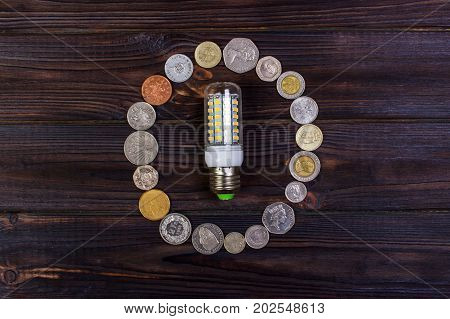 light bulb on over pile of coins - money finance savings concept and idea