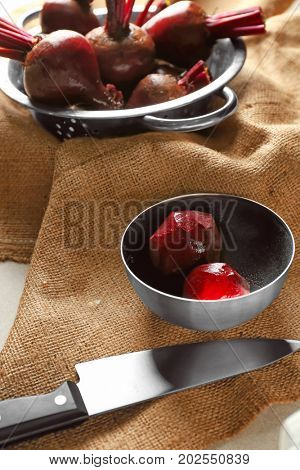 Bowl with peeled ripe beets and knife on table