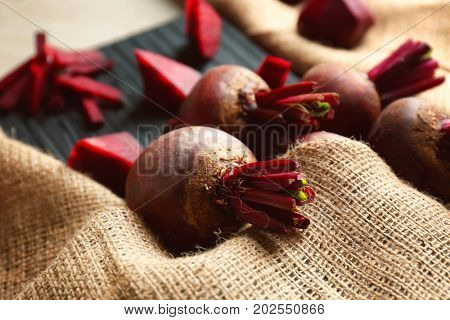 Wooden board with delicious ripe beets on table, closeup