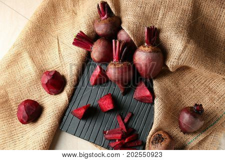 Wooden board with delicious ripe beets on table