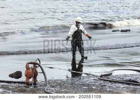 RAYONG THAILAND - JULY 31 2013: A worker in biohazard suit during the clean-up operation from crude oil spilled into Ao Prao Beach on July 31 2013 in Rayong province Thailand.