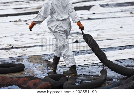 A Worker in biohazard suits used Oil Containment boom as cleaning crude oil from the beach