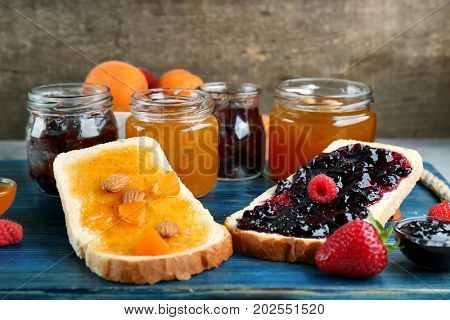 Two slices of bread with apricot and berry jams on table