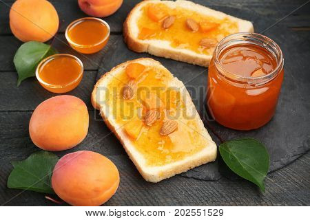Two slices of bread and jar with apricot jam on table