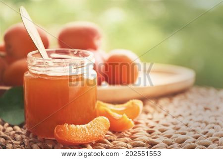 Apricot jam in jar with spoon on wicker mat