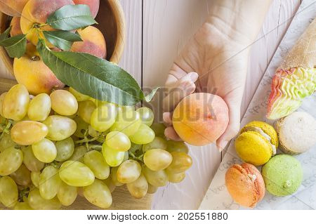 Hands of a young woman holding a peach. Woman making a choice between sweets and fruits made a choice in favor of fruits and holding peach. Unhealthy vs healthy food top view.
