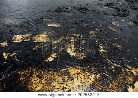 Texture of Crude oil spill on sand beach from oil spill accident