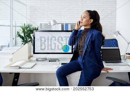 Attractive Filipino business lady sitting on her table and calling on the phone