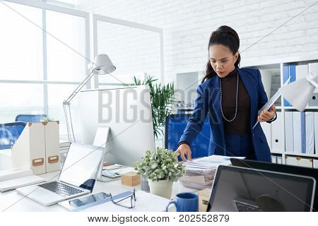 Filipino female entrepreneur taking financial document from the table