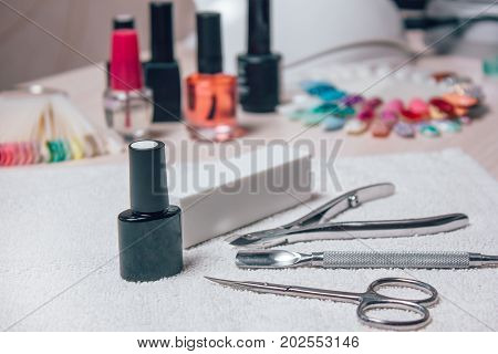 Manicure set for gel nail procedure - colored gel varnishes, scissors, tools, cuticle remover color palette and white file on white table