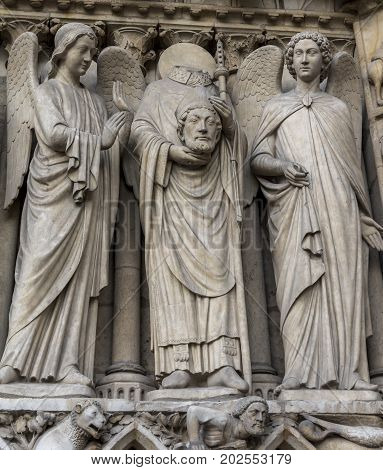 Intricate carvings of Catholic saints on the exterior walls of Notre Dame Cathedral, Paris, France. One of the statutes is holding its head, in its hands.