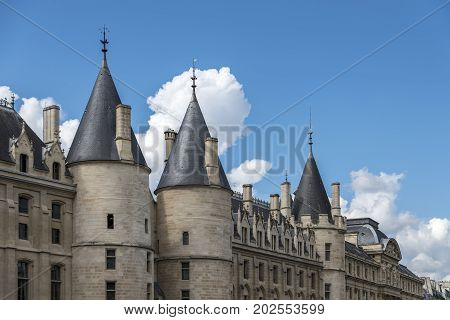 Ancient stone building on the banks of the river Seine, Paris. The building has impressive turrets along the exterior wall