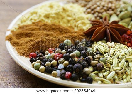 Various spices (cardamom, paprika, coriander, fennel) on a wooden background