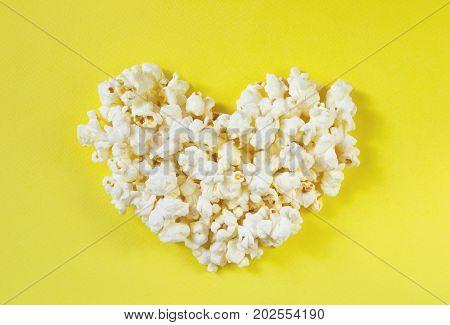 Love cinema concept of popcorn. Heart shaped white fluffy popcorn on yellow retro background